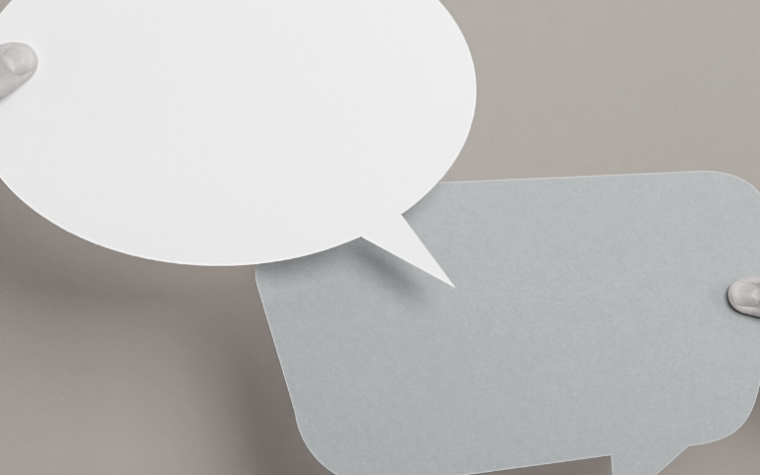 large speech bubbles being held by two hands